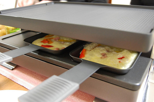 Swiss raclette cheese being melted and scraped