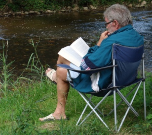 old-man-reading-near-river-germany