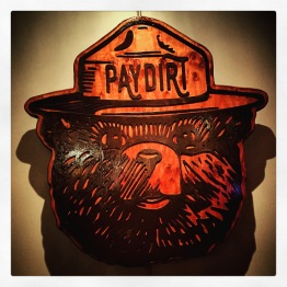 """Isn't that Smokey the Bear? Hero of forest fire prevention since like 1944? Well, I guess he's slinging pints at a pub called """"Paydirt"""" now. Jesus. Talk about your lateral career moves..."""